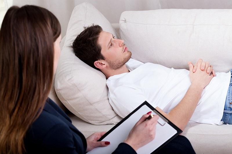 Rapaz em tratamento do ciúme com seu psicanalista no divã
