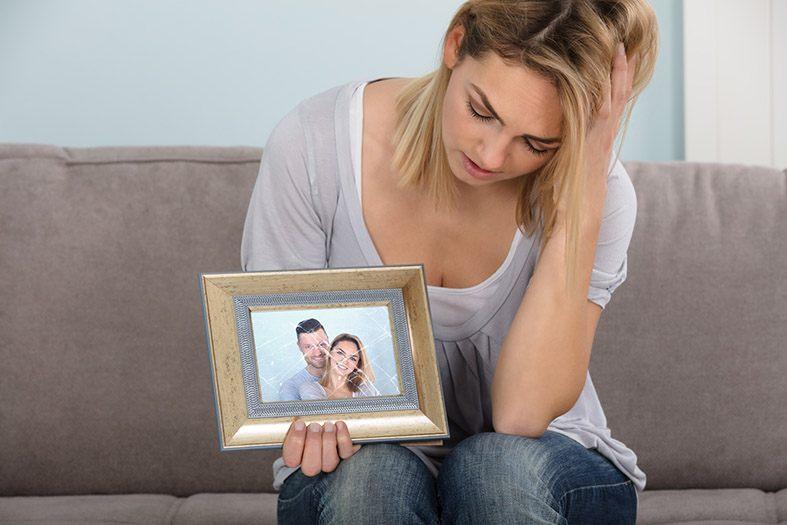 Mulher sofrendo porque sente saudades do seu ex-marido olhando para uma foto do casal