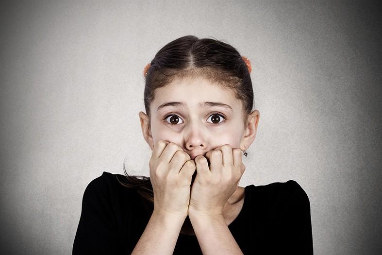 Menina assustada, com medo das responsabilidades pois não é mais criança